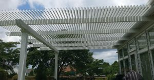 White pergola attached to a home over a patio
